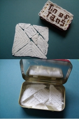 Crocheted tangram pieces forming a square, the tin of tans cover, the tans fit inside an Altoids tin.