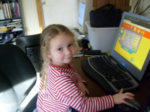 My daughter, K, using the computer to play on the Curious George website