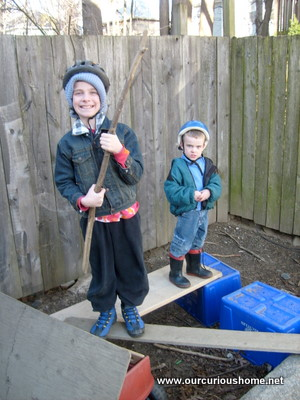 The boys dressed warmly with bicycle helmets on recycling bins and boards
