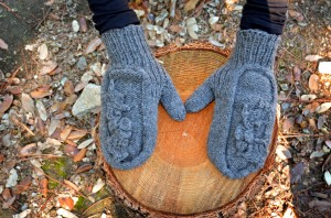 The Holly Mittens from above, resting on a stump