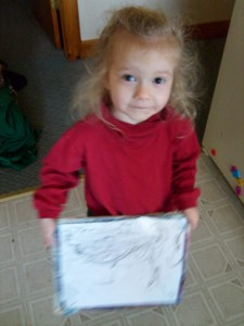 K showing the camera the white board drawing she did during M's school
