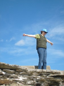Aunt B at Beavertail Lighthouse rocks, spreading her arms to the wind and the sunshine