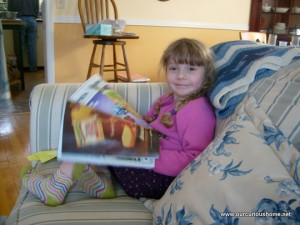 K reading a magazine on Grandma's couch
