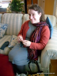 Christine Guest knitting a glove on her mom's couch