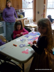 K and a friend glueing die cut hearts into animals