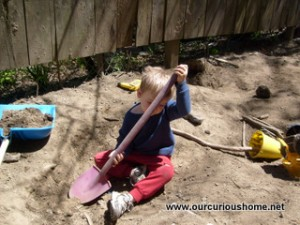 M playing in the dirt at the side yard