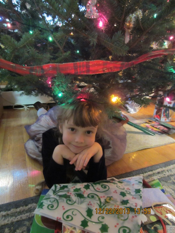 K under the tree at Grandma's house in her dressy Christmas Eve dress