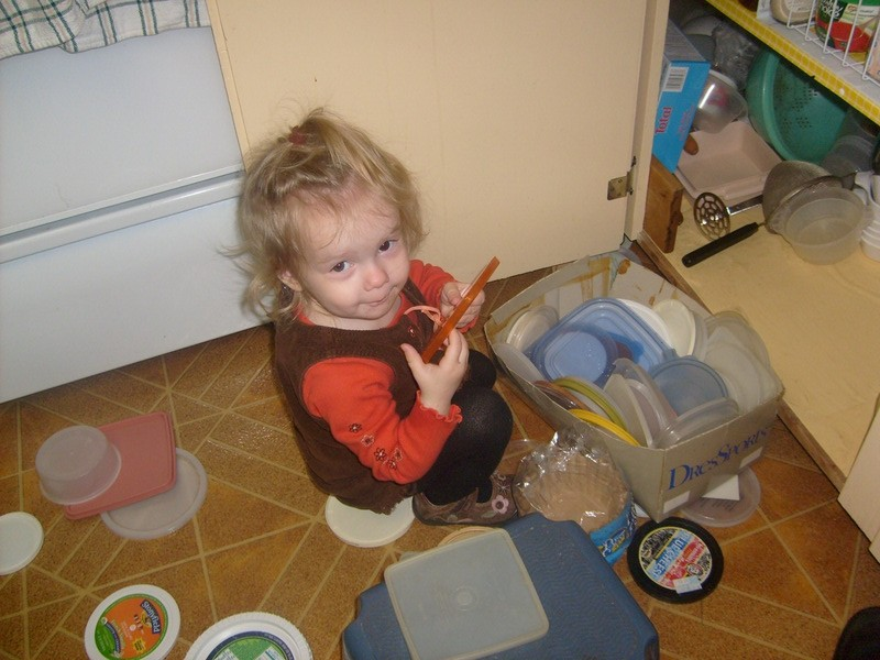 K getting into plastic lids at my Mom's kitchen. Apparently no one minded because we took a picture.