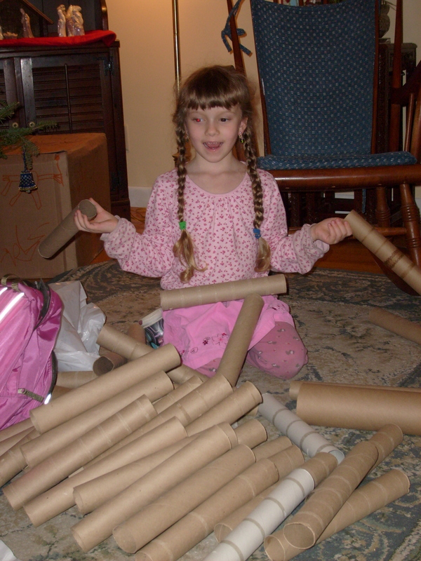 K in a pink ensemble playing with about 30 cardboard tubes