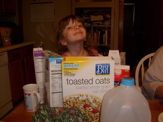 K hiding behind cereal boxes at breakfast