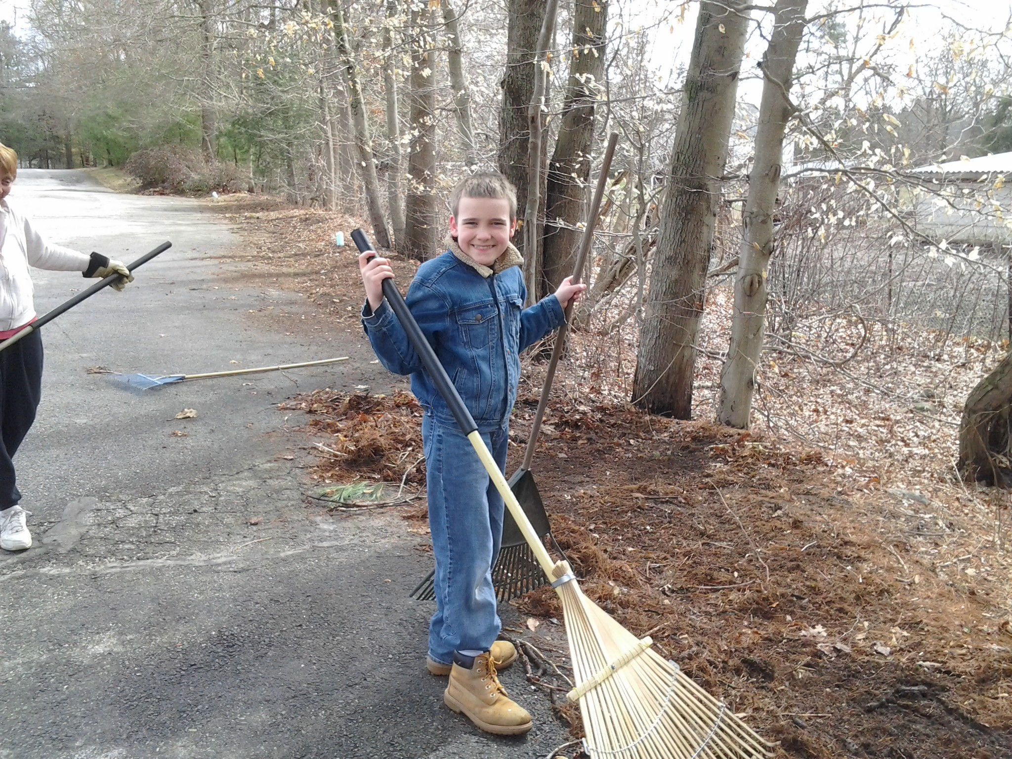 M raking leaves with two rakes at church workday