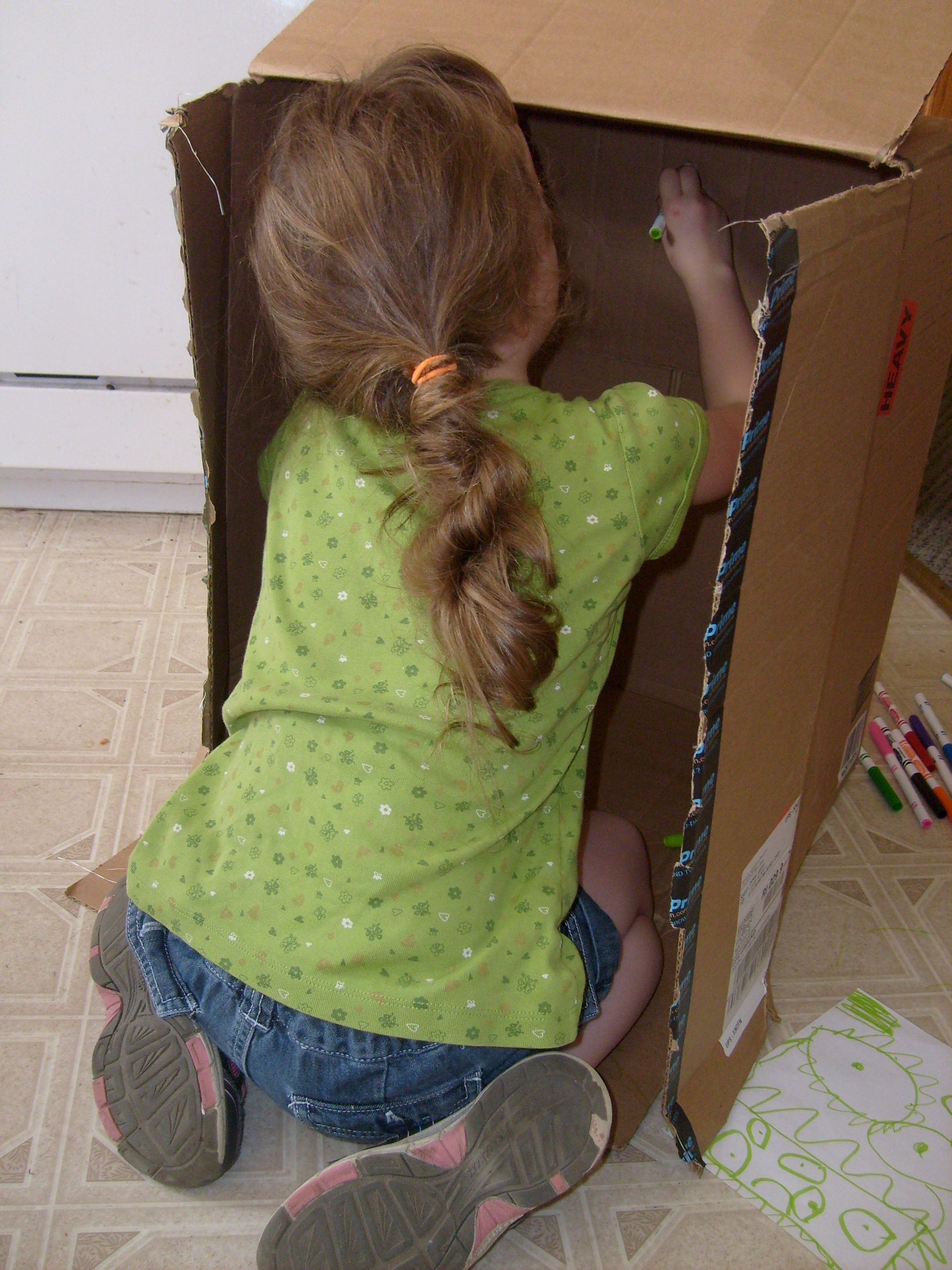 K's back as she draws on the inside of the best toy in the world - a cardboard box