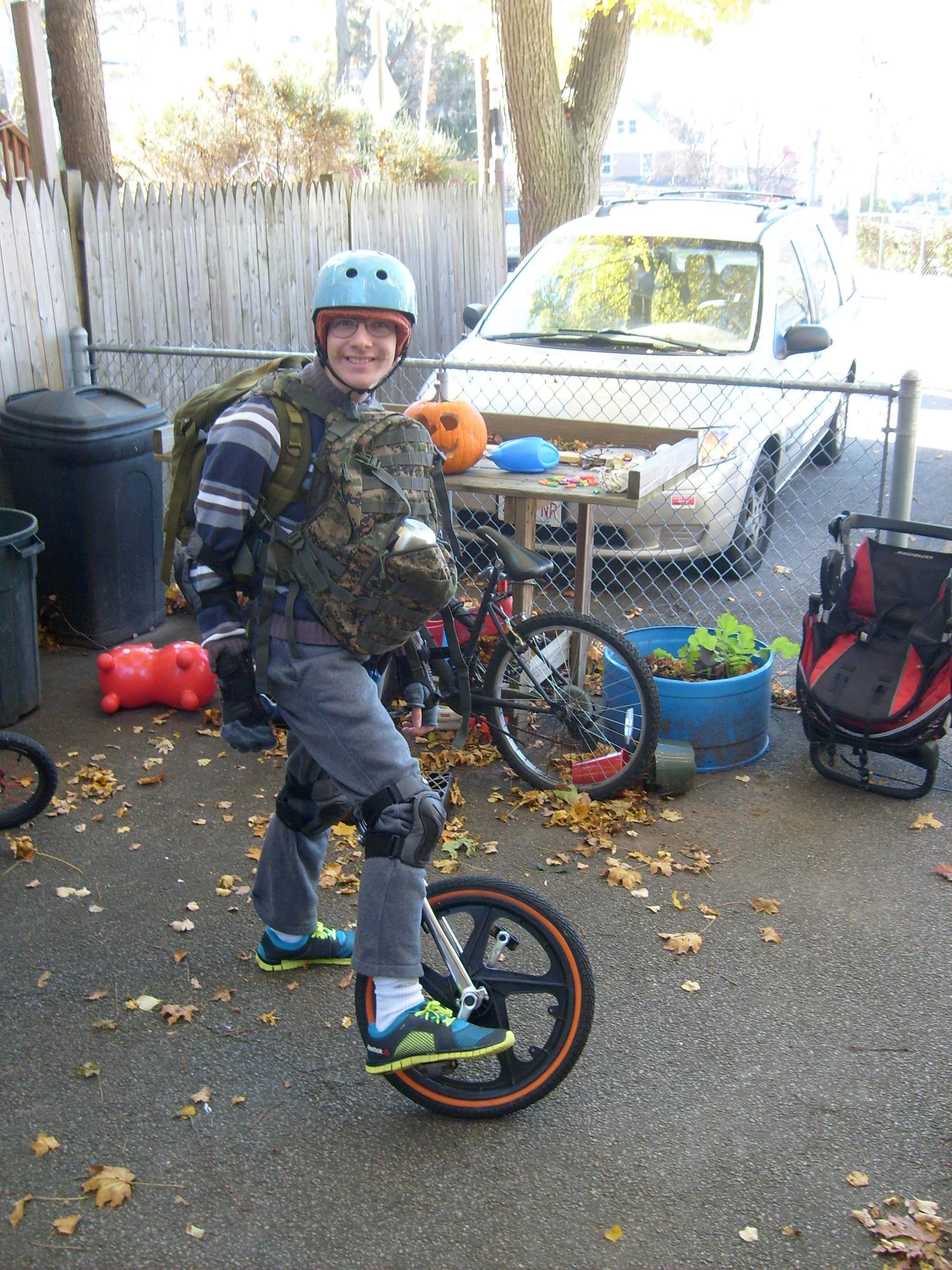 Ben wearing two backpacks and riding his unicycle