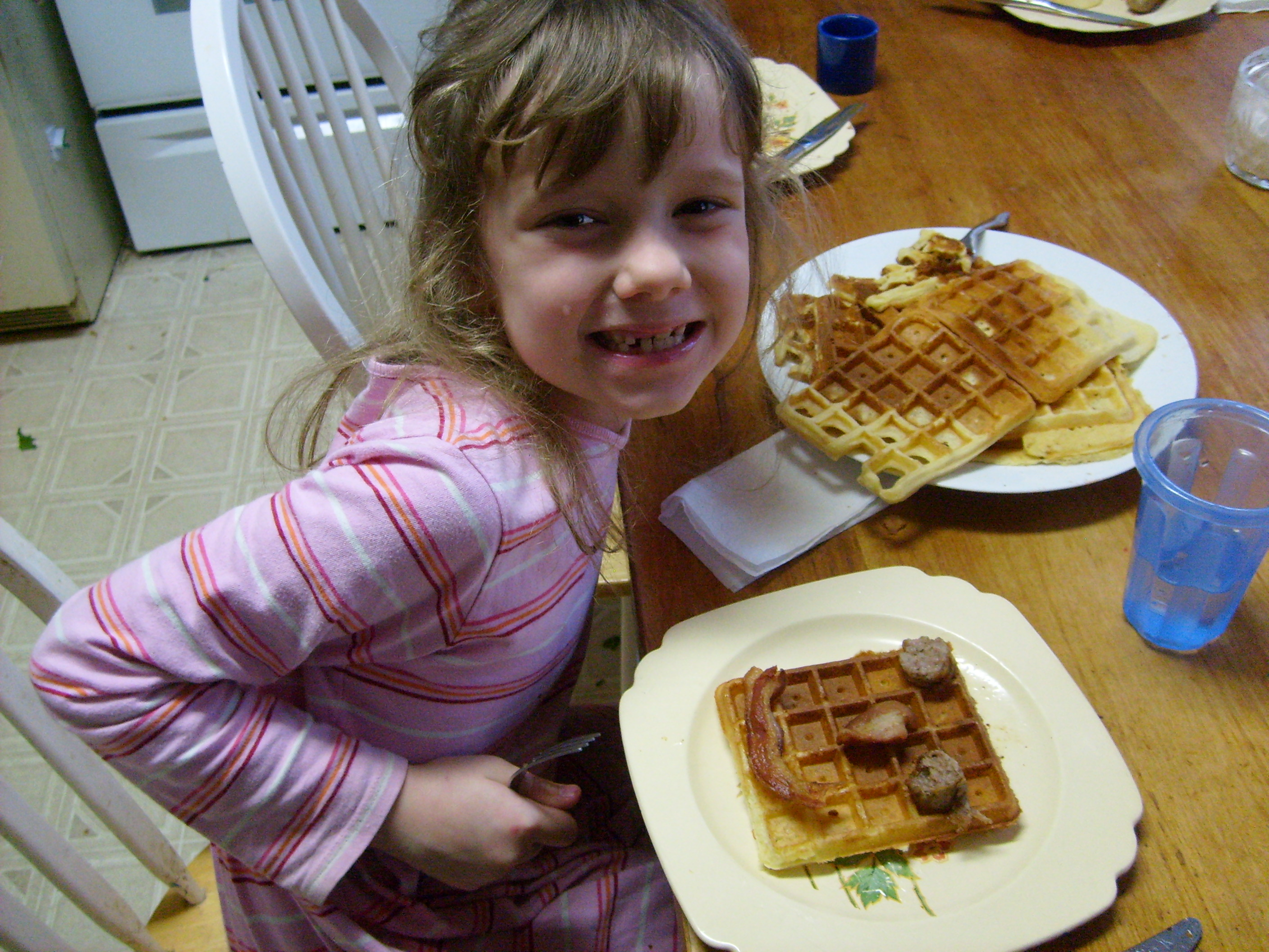 K with her waffle face: bacon for mouth, two pieces of sausage for the eyes