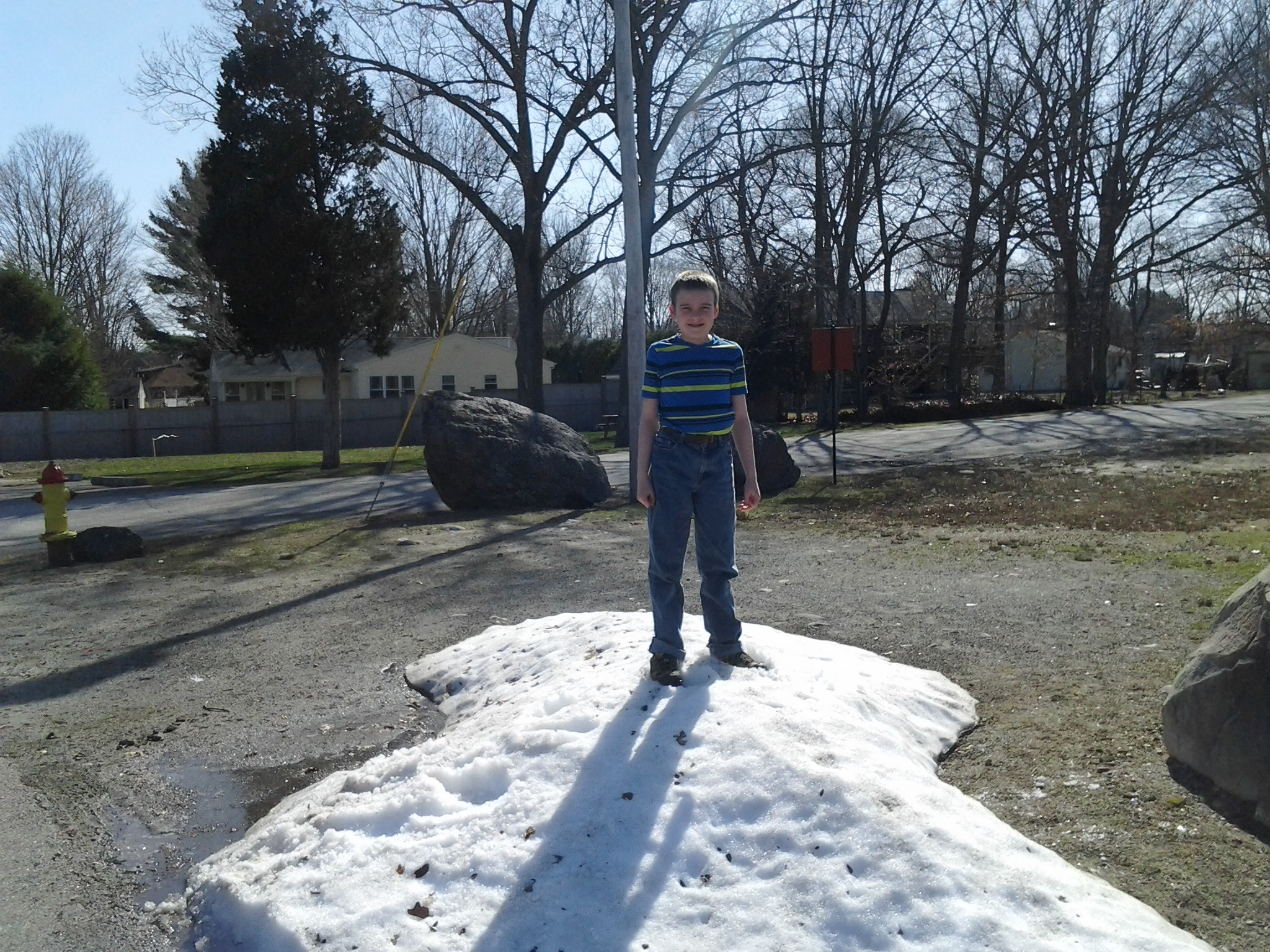 M wearing short sleeves and jeans, standing on a pile of un-melted snow, in early April