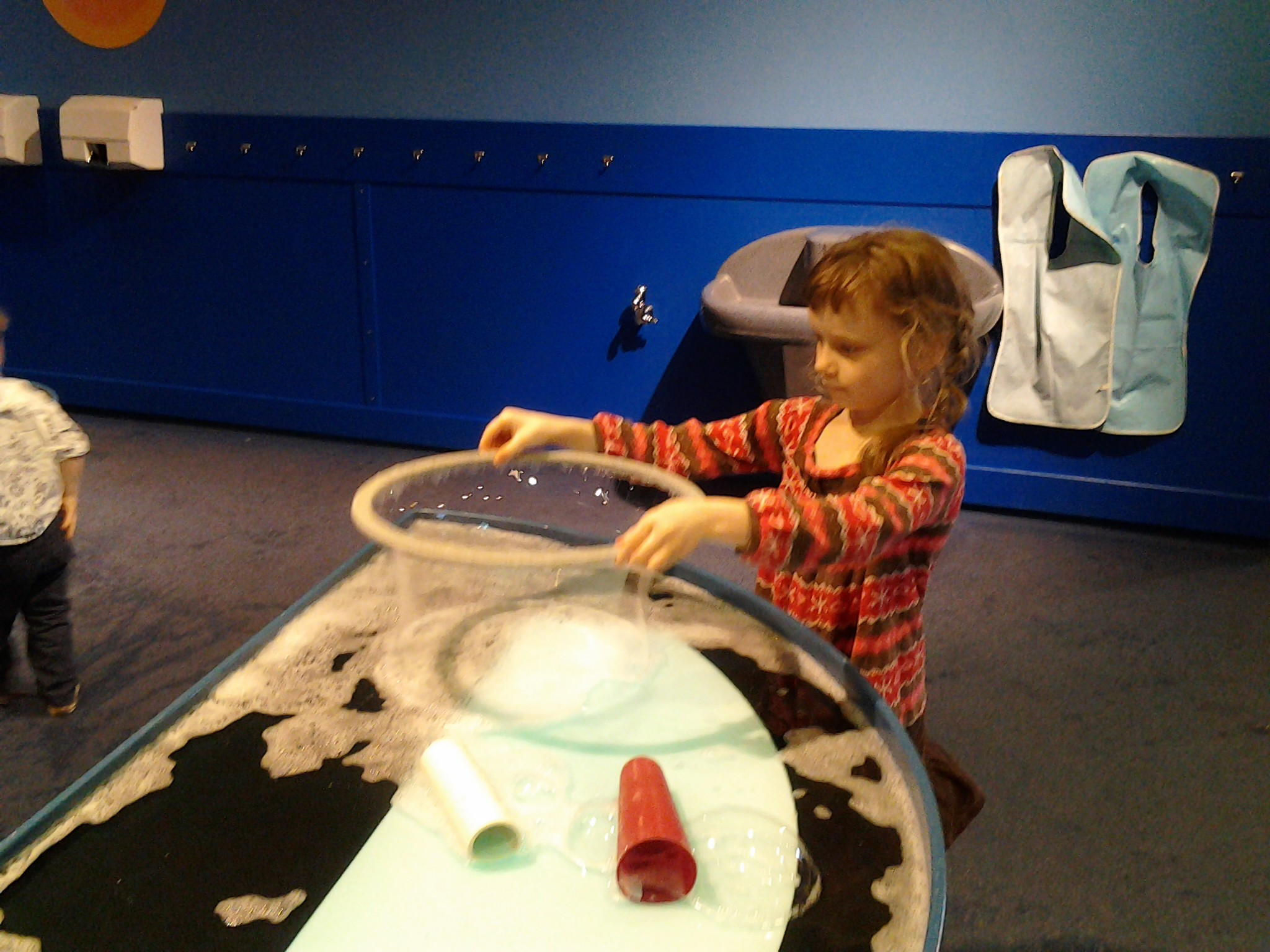 K making a huge bubble with a hoop in a pan of bubbles at the Boston Children's Museum