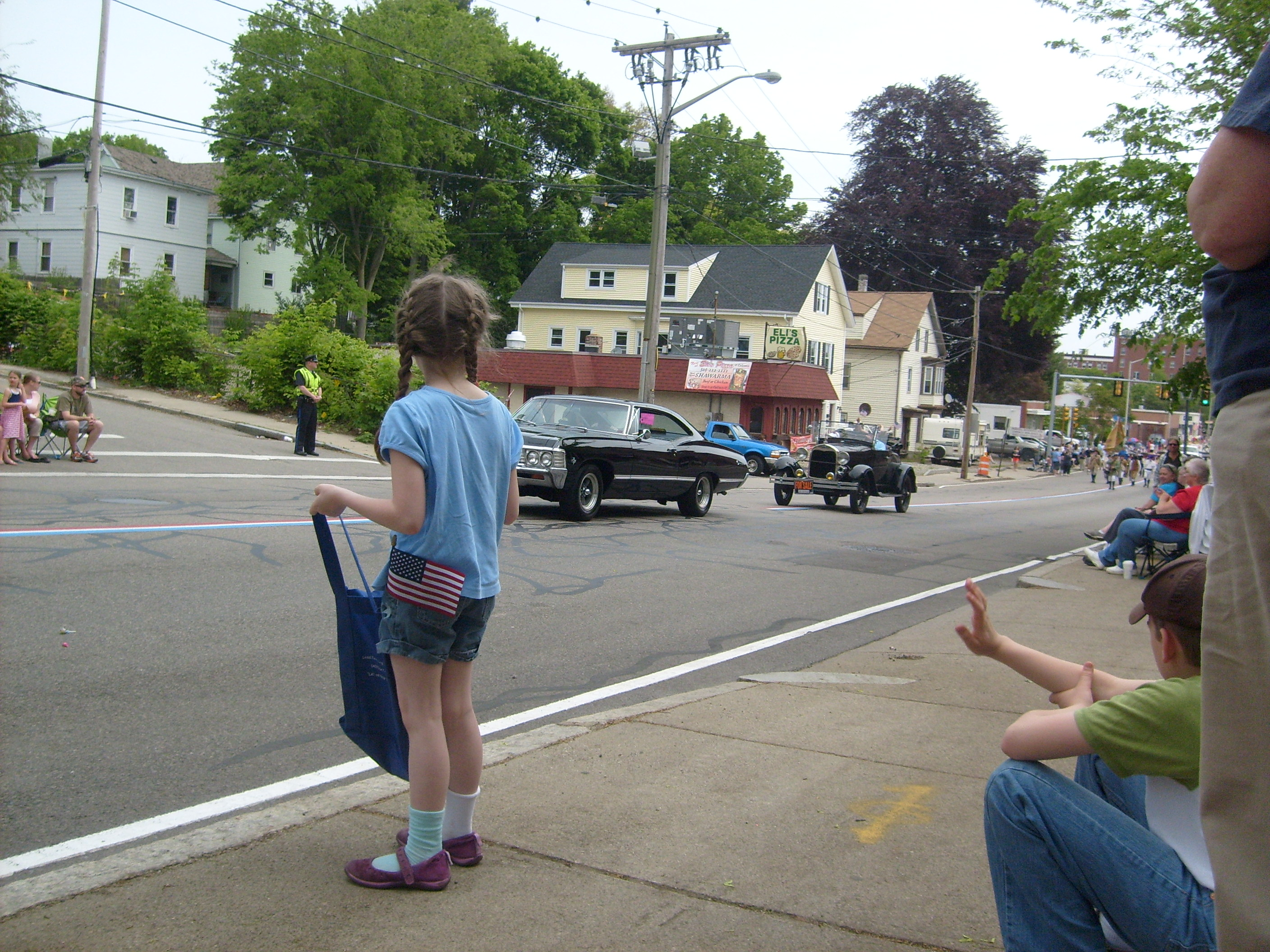 K holding her candy bag open at the Memorial Day Parade, because some of the guests in the fancy cars like to aim candy at open bags, and if they miss, they throw again.