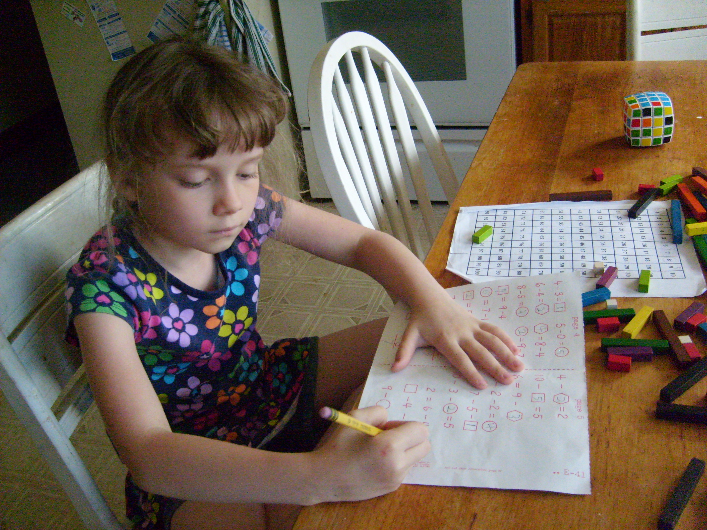 K at the kitchen table, surrounded by math stuff