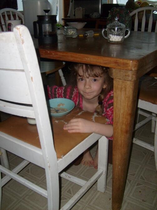 K eating breakfast under the kitchen table