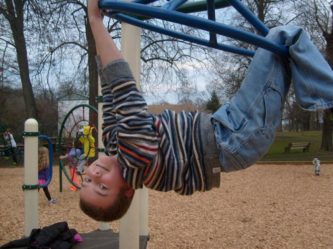M hanging from monkey bars