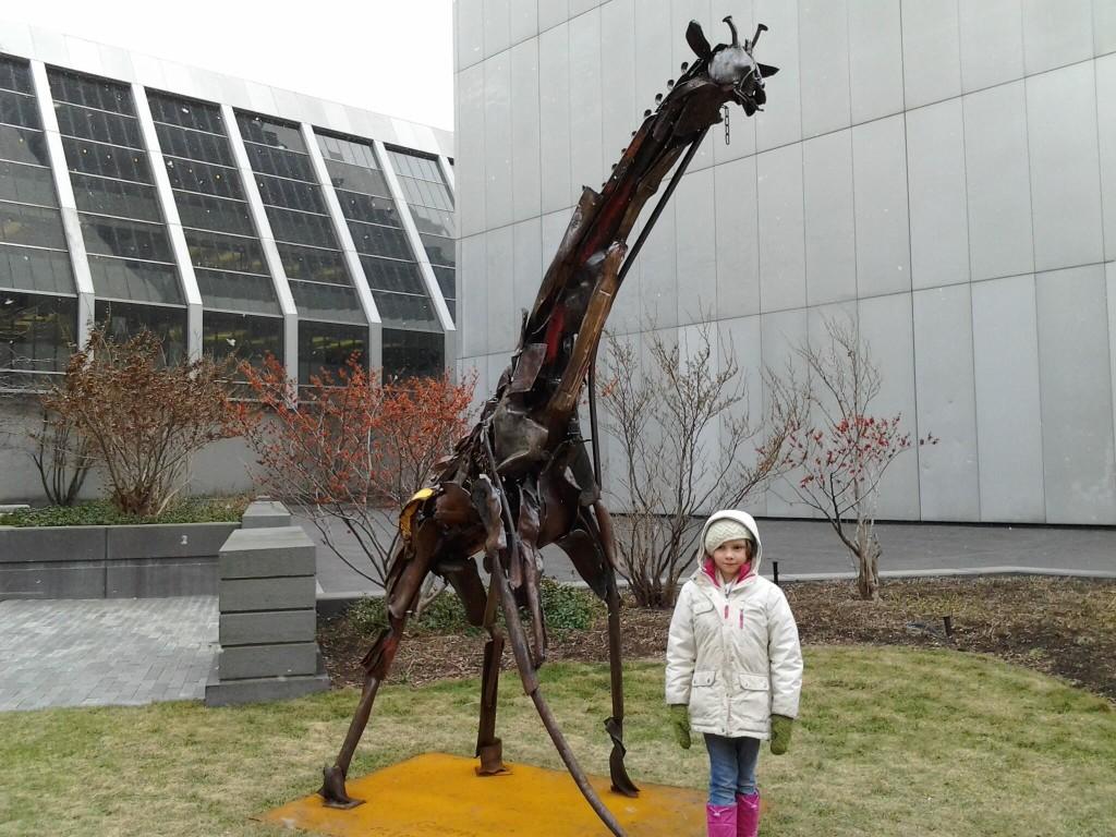 k by a giraffe statue