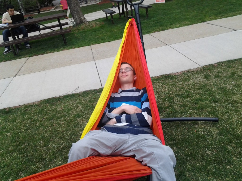 Benjamin, in a hammock, practices being a hard working student on the quad.