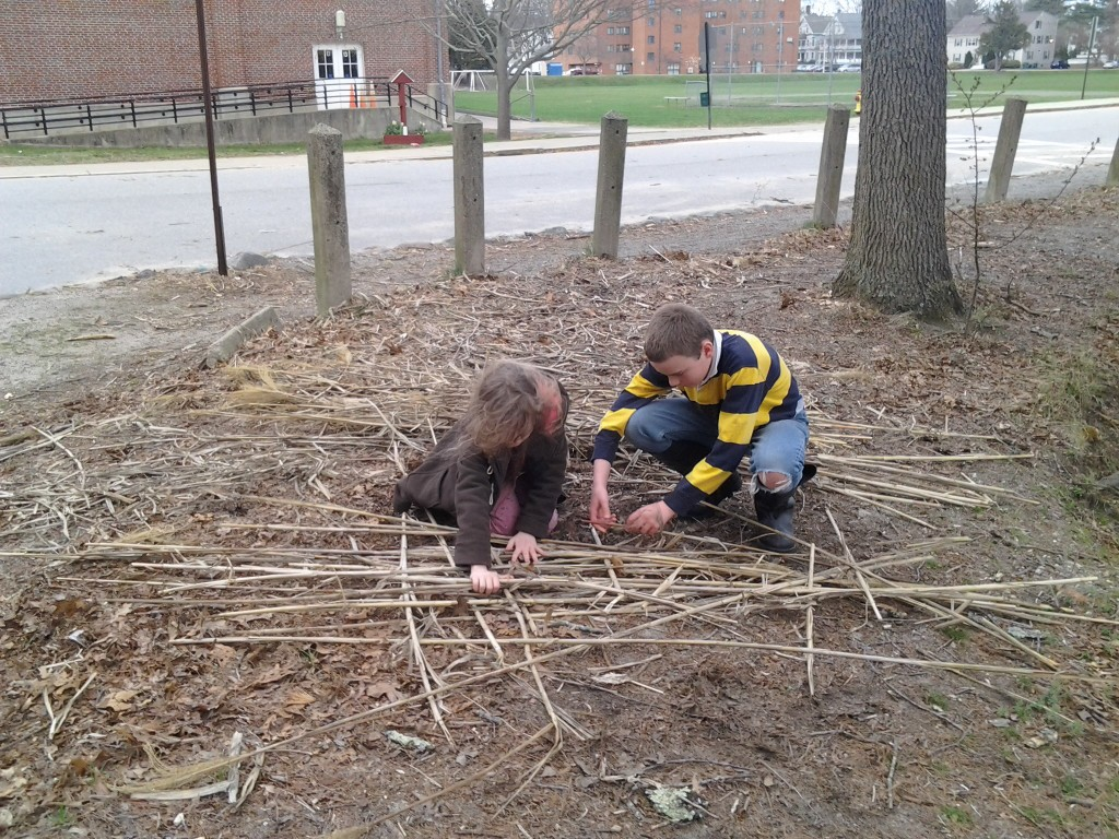 M and K begin constructing a raft from a pile of reeds.