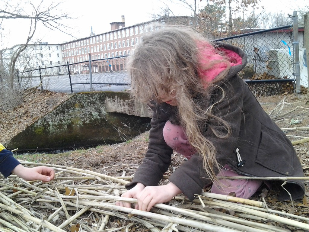 K continues to work on the reed mat raft.
