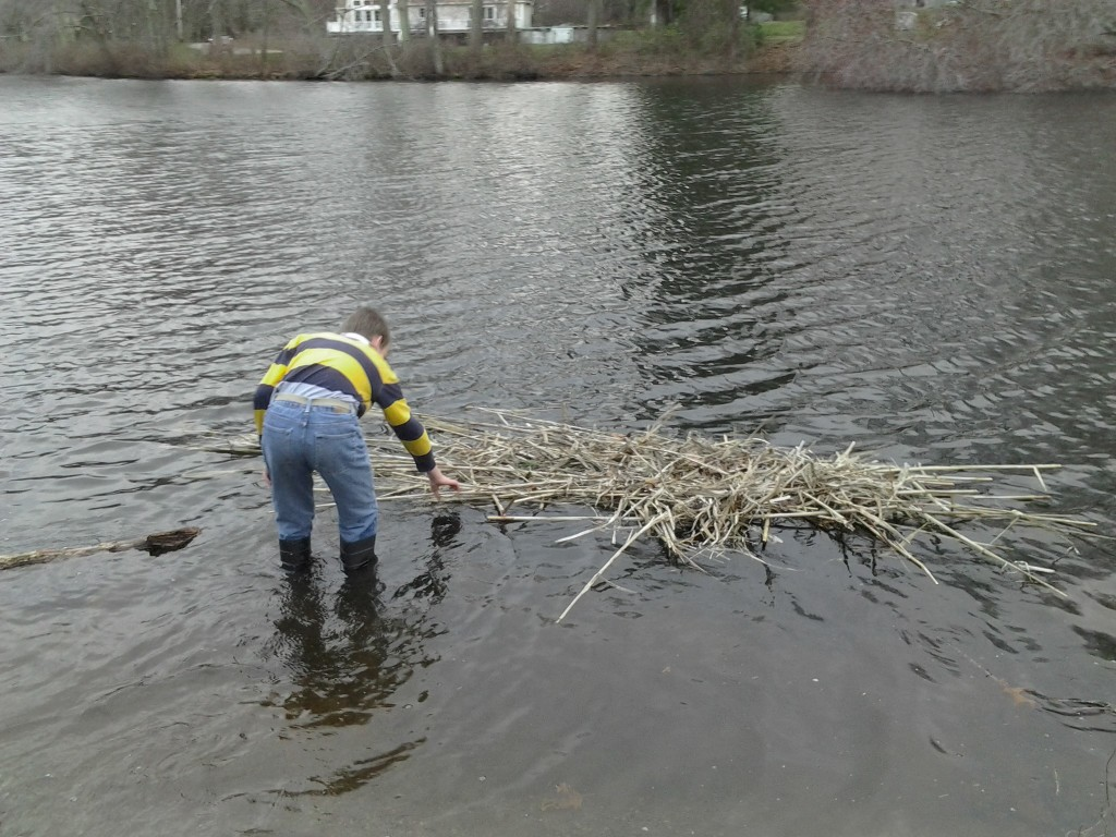 M stands in the water, examining the raft
