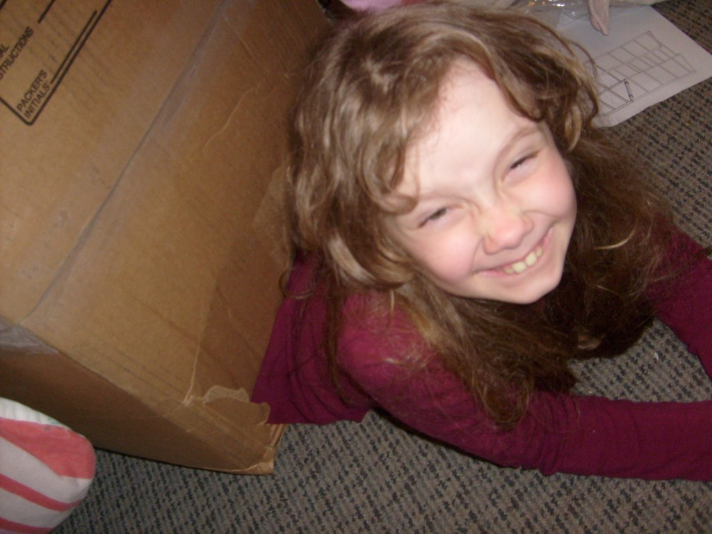 K grinning as she crawls out of her box