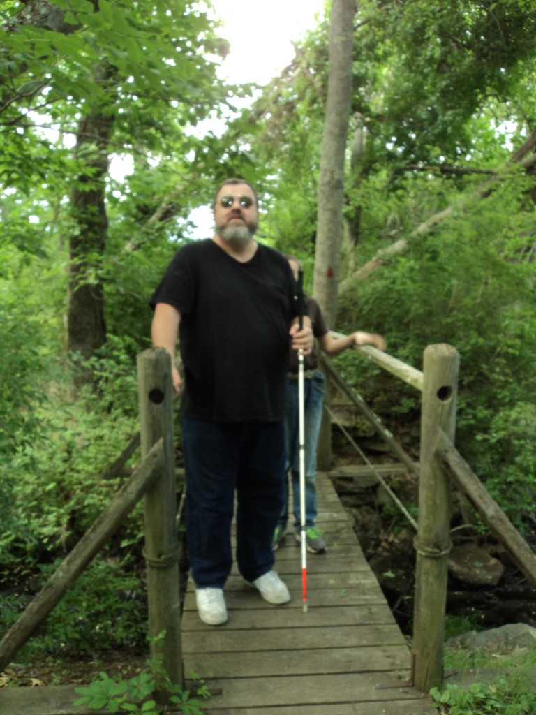 Warren ane walking across a narrow foot bridge