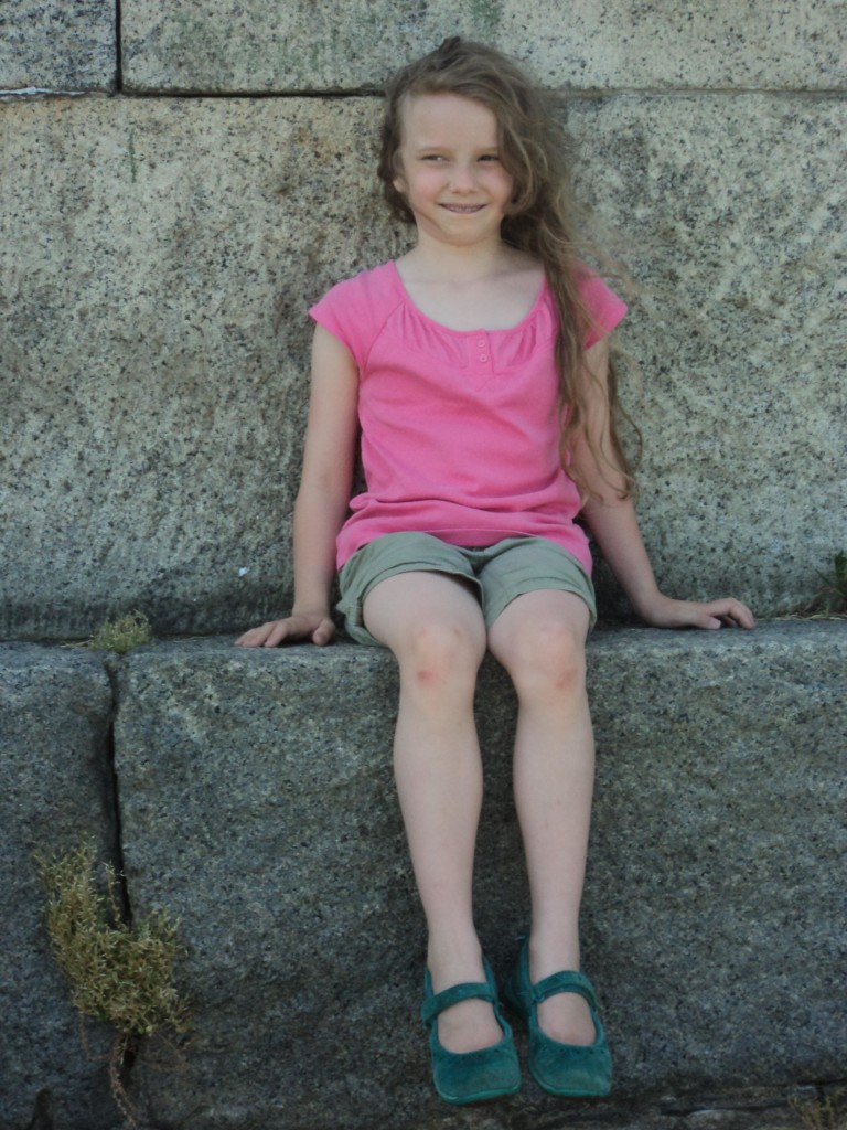 K sitting on a stone wall
