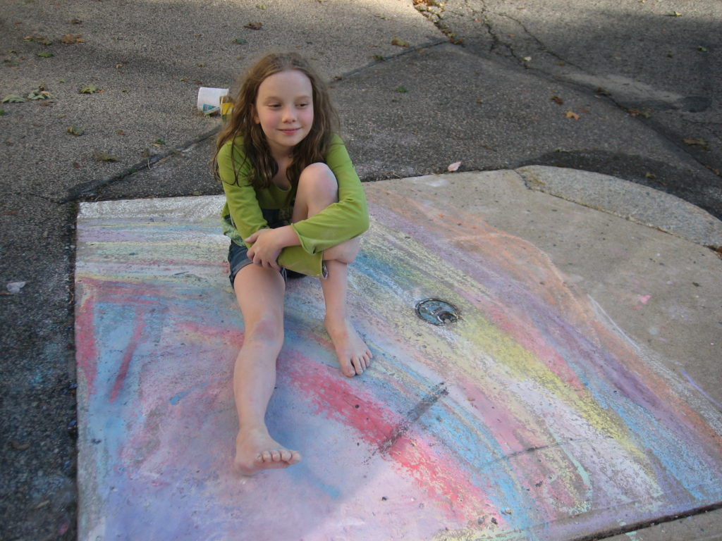 K sitting on sidewalk chalk rainbow