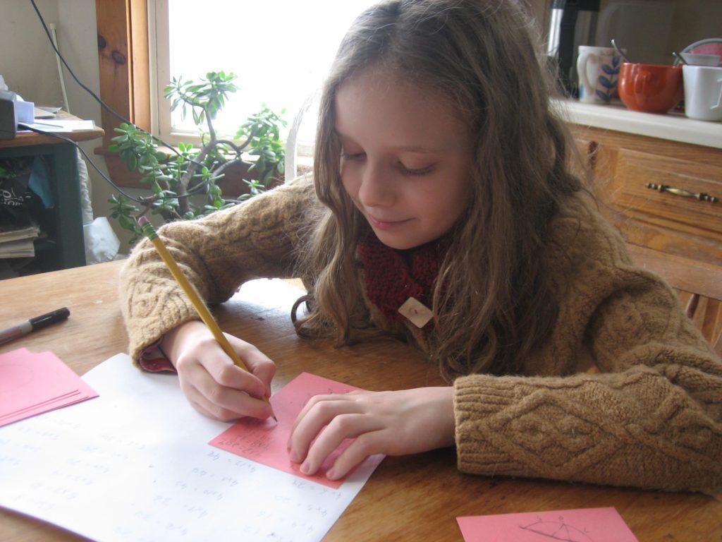 Kari doing copywork with wearing her cowl
