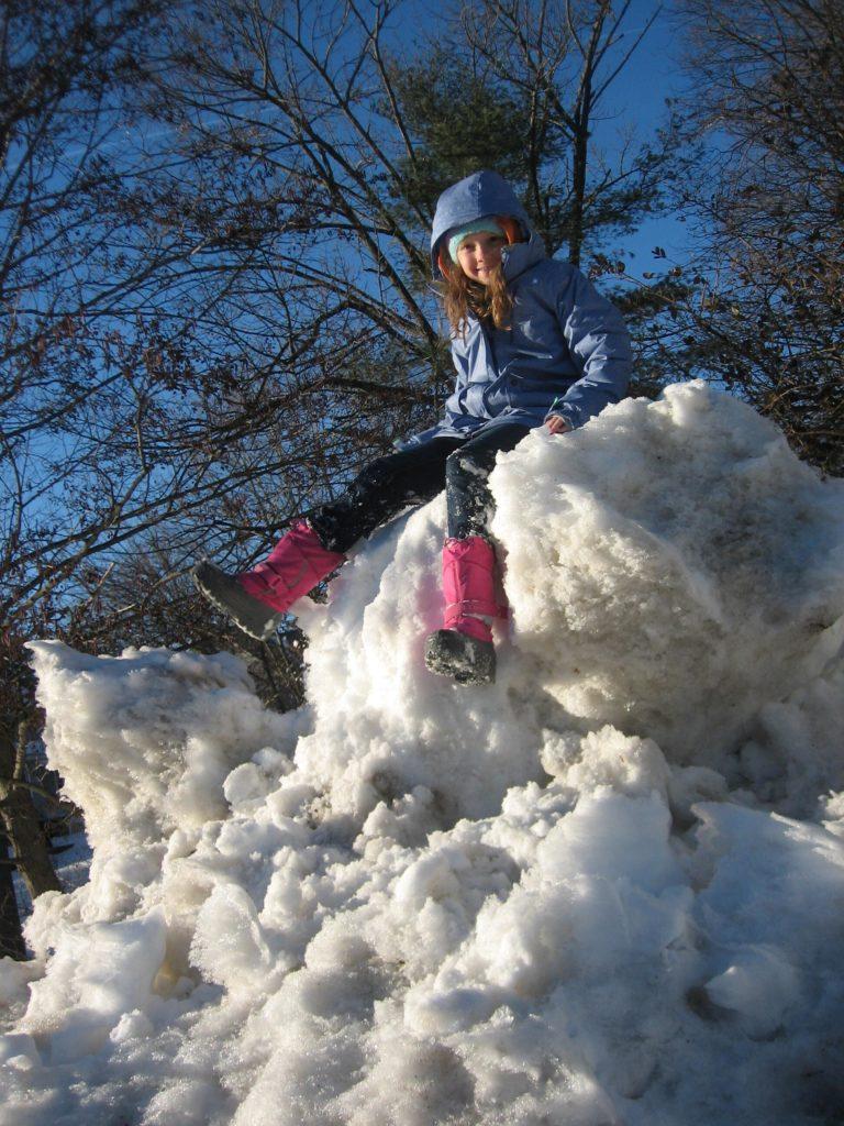 K sitting on a huge snowpile