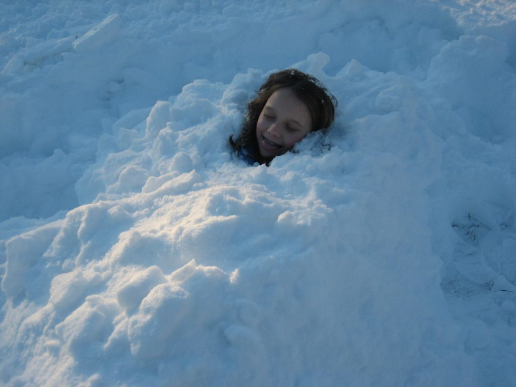 K buried in snow pretending to be a zombie