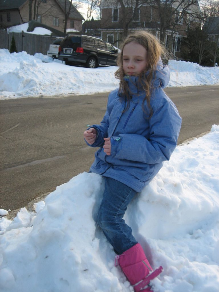 K pretending to ride a pony while sitting on a snow bank