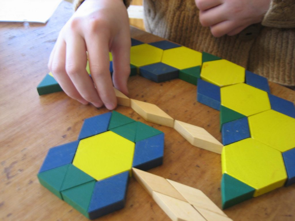 K's hand making a bow out of pattern blocks